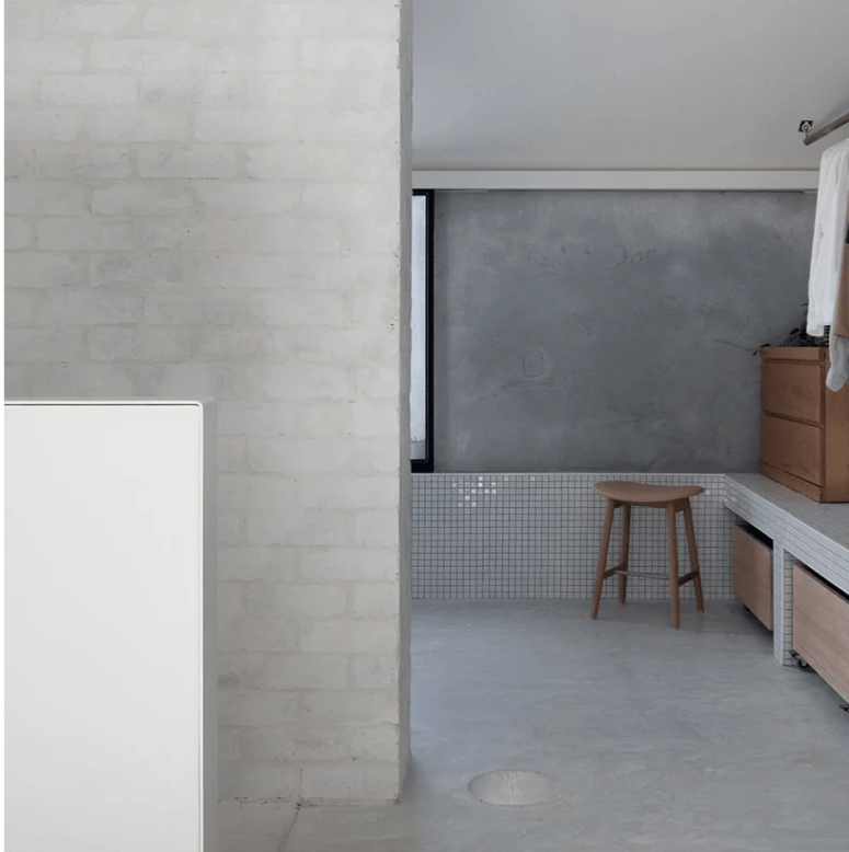 The bathroom shows off how to combine plaster, concrete and brick plus white tiles harmoniously in one space and add wood to it for a warmer look