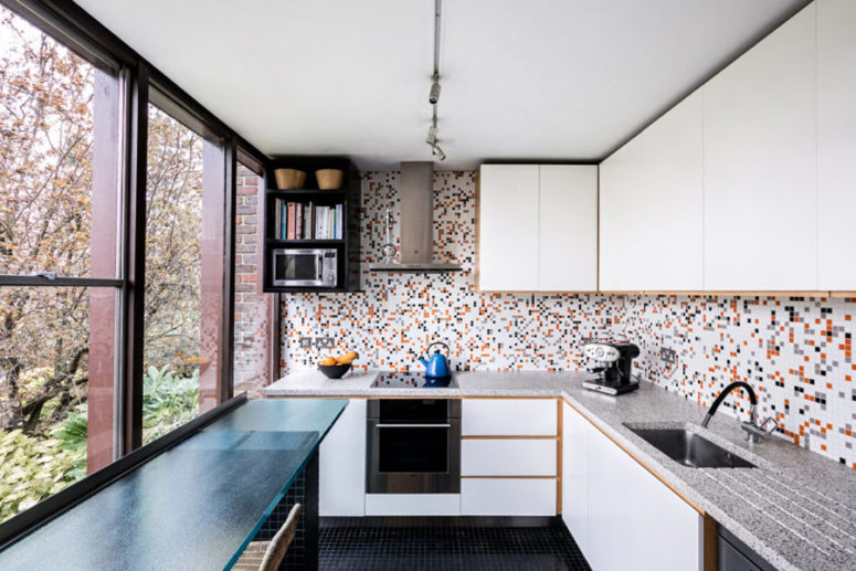 The kitchen is done with a colorful backsplash and sleek white cabinets, amazing views make it wow
