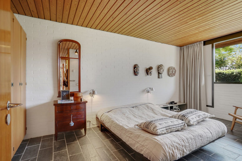 The master bedroom is done with a large bed, wardrobes, a dresser of redwood and somemasks on the wall