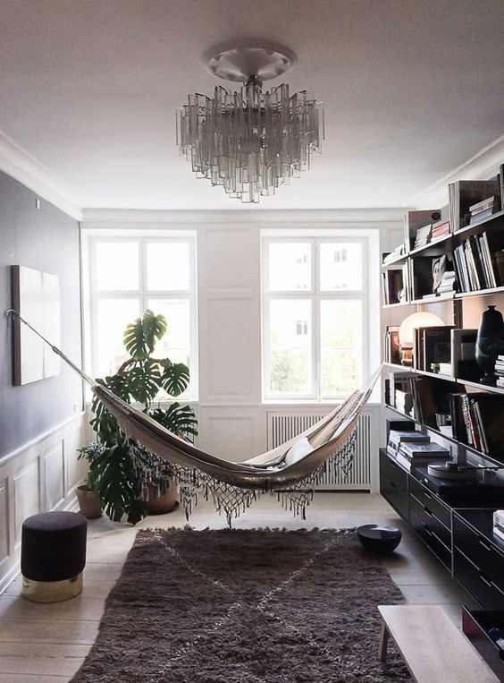 a gorgeous reading nook with a hammock, a rug, ottomans and a bookshelf that separates the nook from the rest of the space