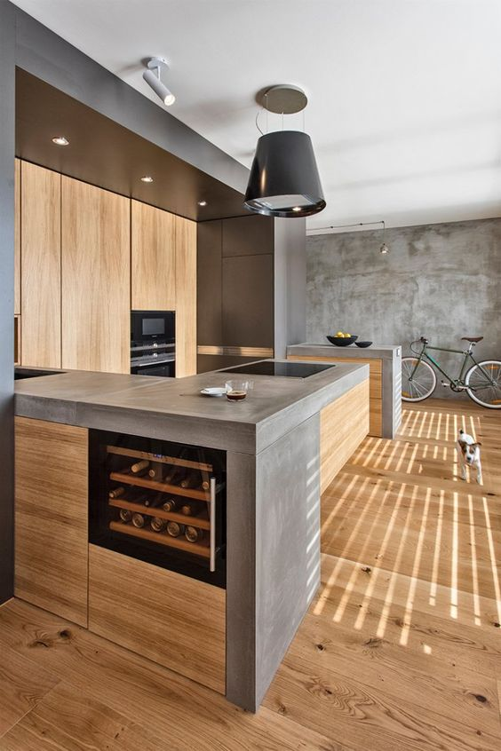 A Minimalist Industrial Kitchen Of Light Colored Wood With Concrete  Countertops Plus Metal Touches
