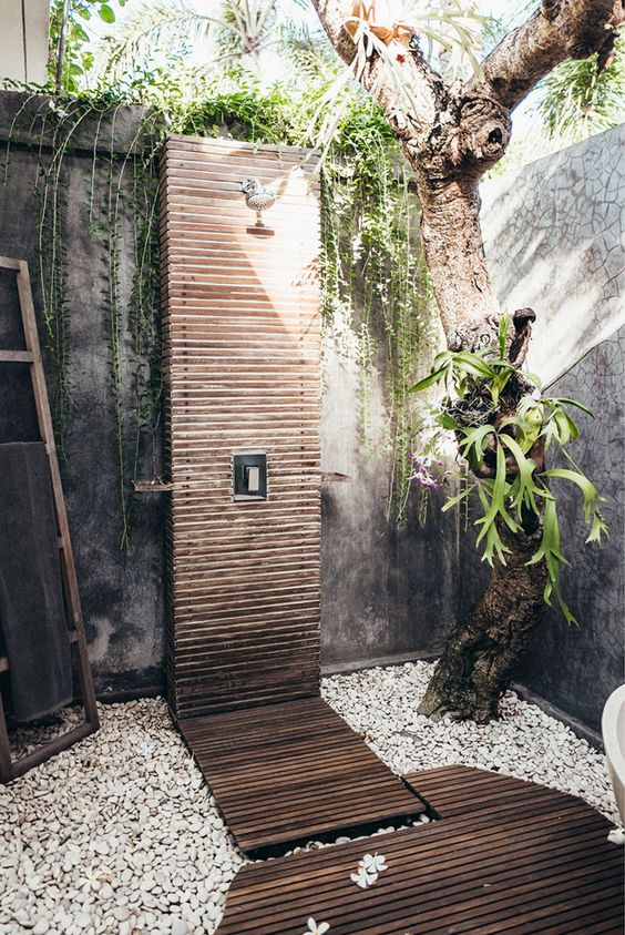 a spa-like outdoor shower with pebbles, living plants and a tree and a wooden clad shower and a deck