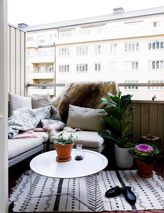 a welcoming nook with an L-shaped bench, potted plants and a small coffee table