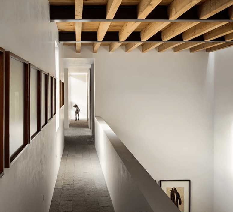 The ceilings feature wooden beams that add interest, and there are artworks along the gallery