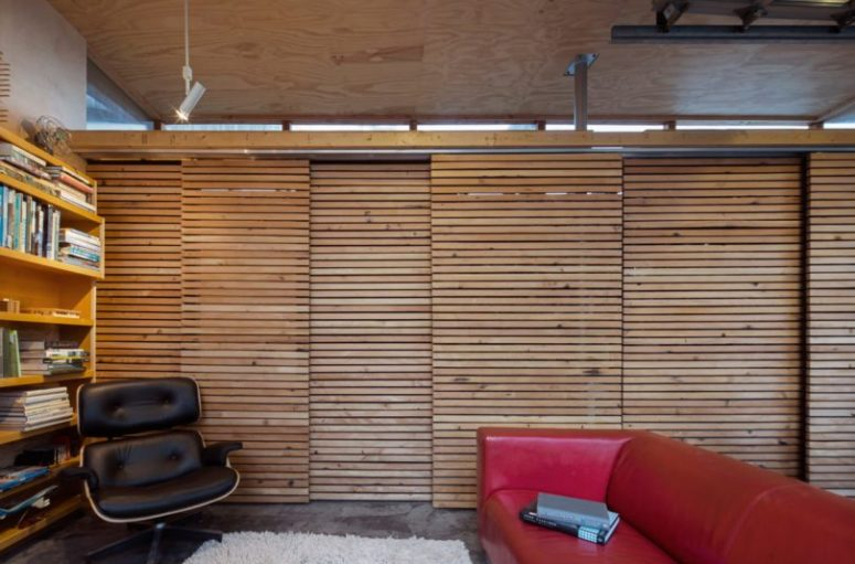 The wall and storage is hidden with wood plank sliding doors to avoid cluttering a small space