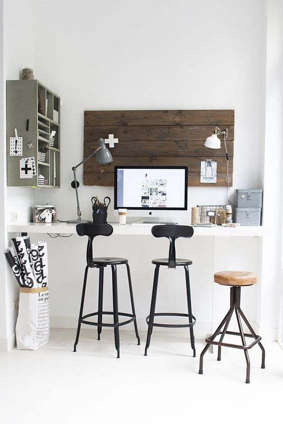 a built-in wall-mounted desk with high stools to sit or stand whenever you want