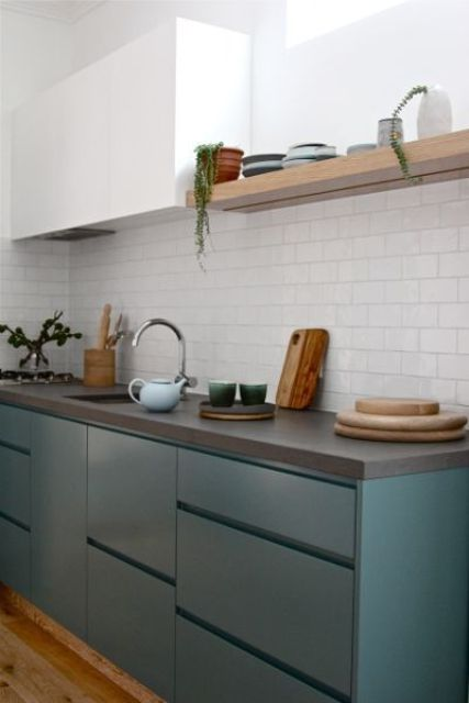 a contemporary teal and white kitchen is spruced up with a cocnrete countertop and a white tile backsplash