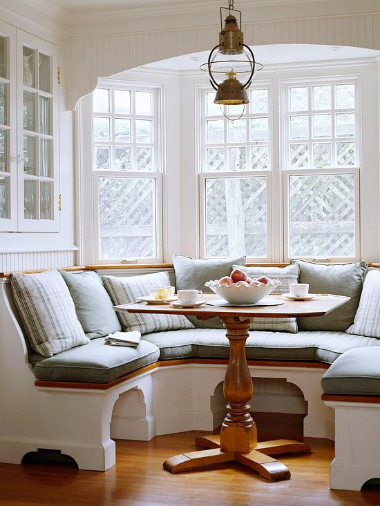 a cozy built-in chalf circle banquette seating with a small rustic table look very inviting