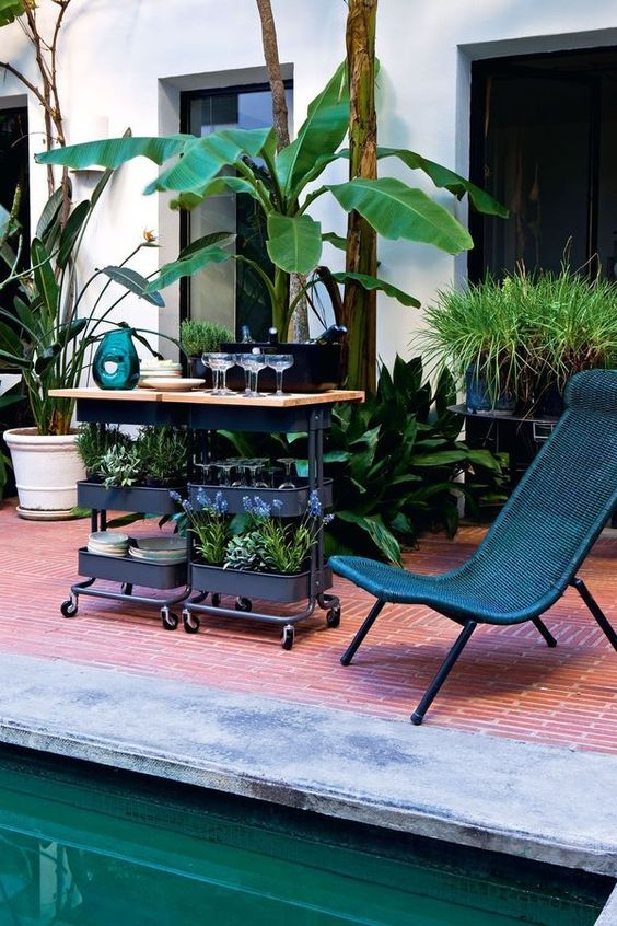 a gorgeous outdoor bar in black with a wooden countertop using two IKEA Raskog carts for storage