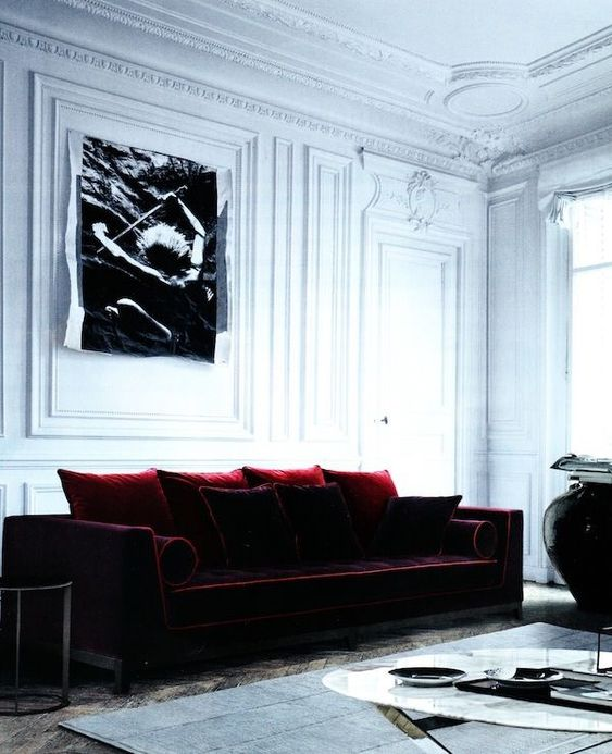 a refined living room with a colorful statement - a burgundy velvet sofa with pillows