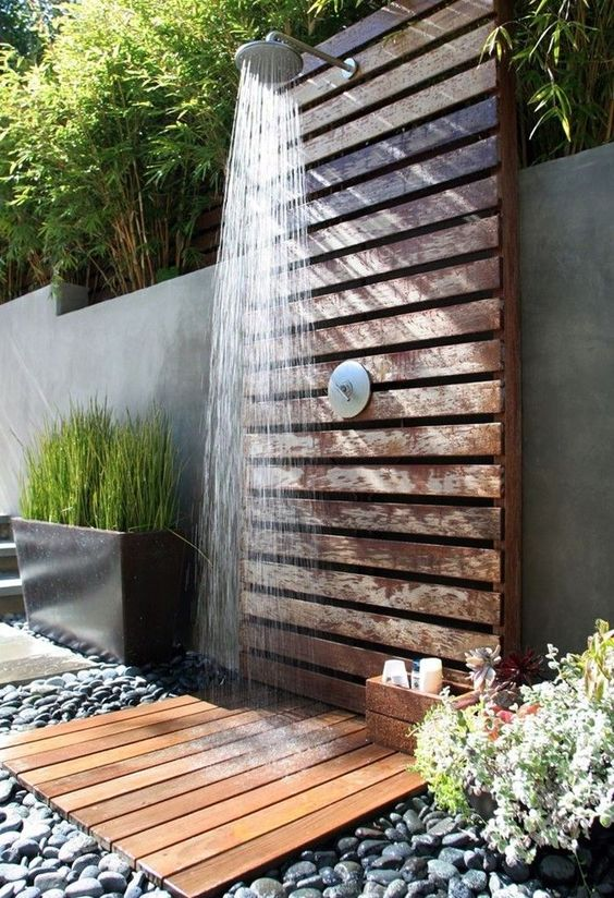a spa outdoor shower of wooden planks with pebbles on the ground and greenery around