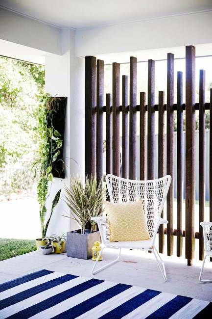 a vertical plank wooden screen is a chic idea for privacy and brings a relaxed feel to the space