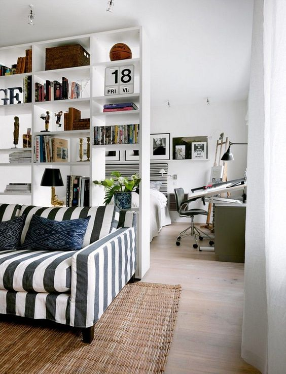 a white shelving unit separates the living room and the bedroom making the latter more private