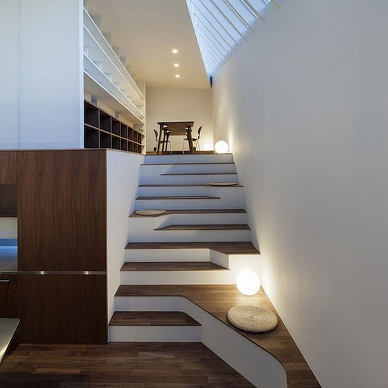an asymmetrical staircase becomes a cool decor feature, and little cushions here and there make sitting spots