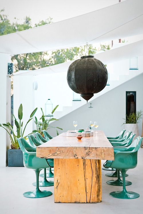 make your outdoor space super trendy with a rough wooden table and sleek plastic chairs in turquoise
