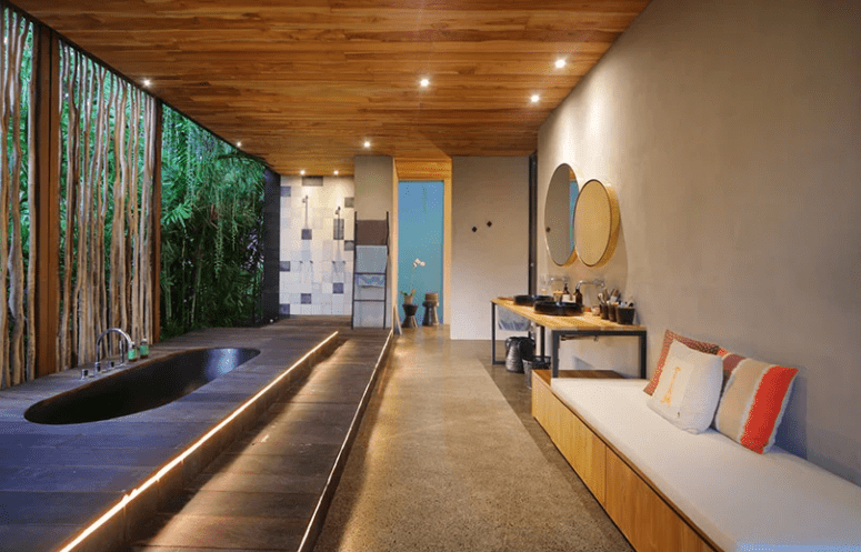 Here's a spa bathroom with a large sunken tub, which is opened to outdoors, yet hidden with a bamboo wall