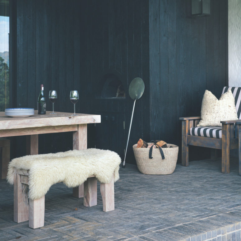 There's a dining zone with a rustic set and a built-in pizza oven