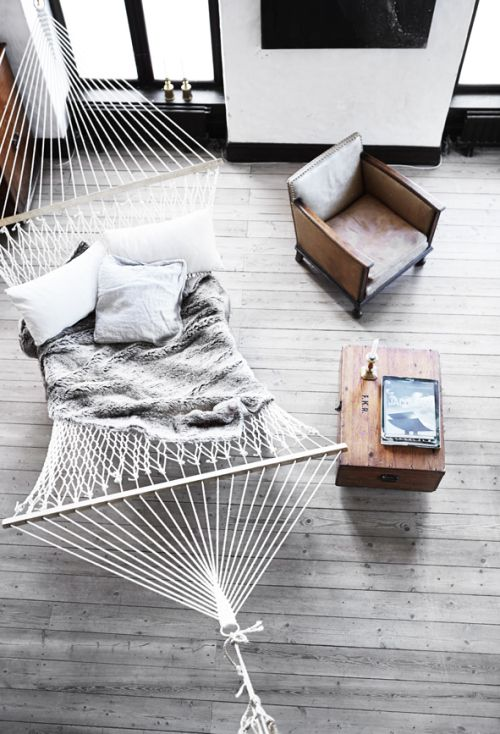 a large hammock with pillows and a blanket instead of a usual couch or daybed in the living room