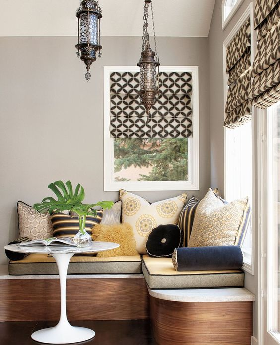 a luxurious banquette seating with lots of cushions and pillows plus storage inside