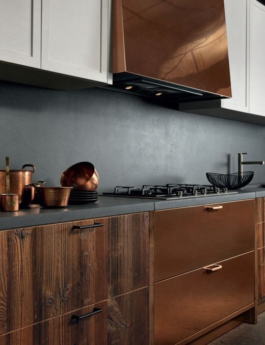 a luxurious kitchen of wood and copper with a concrete backsplash and countertops