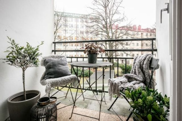 a small balcony with folding furniture, potted greenery and candles for having meals
