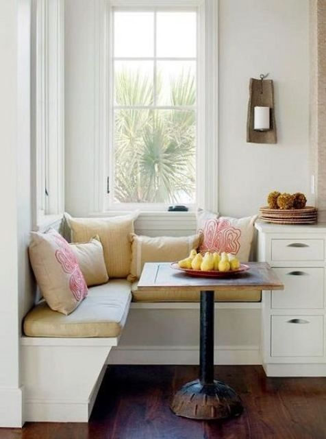 a little breakfast nook with a built-in corner banquette seating and a tiny table