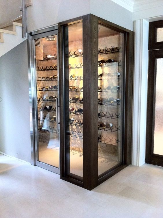 a small yet comfy wine cellar under the stairs with metal holders for bottles on the wall