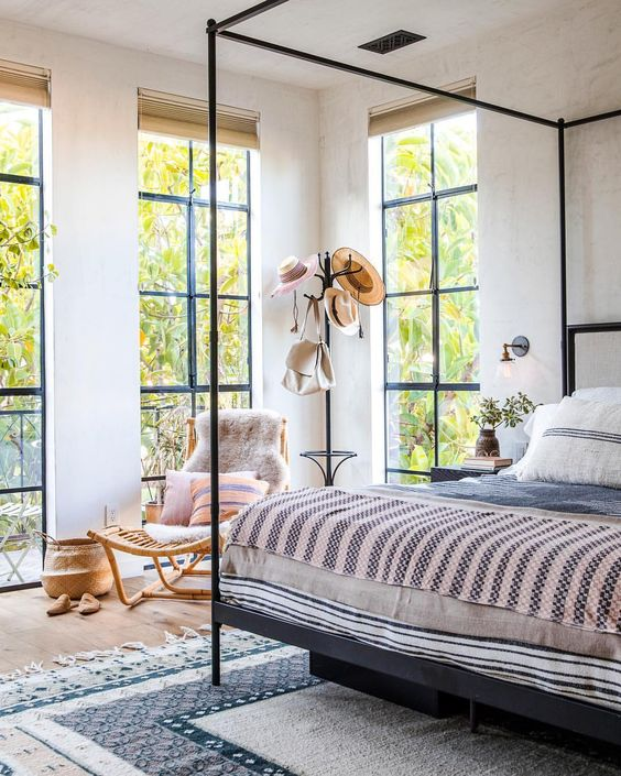 floor to ceiling windows create a light feeling in the bedroom and fill it with natural light