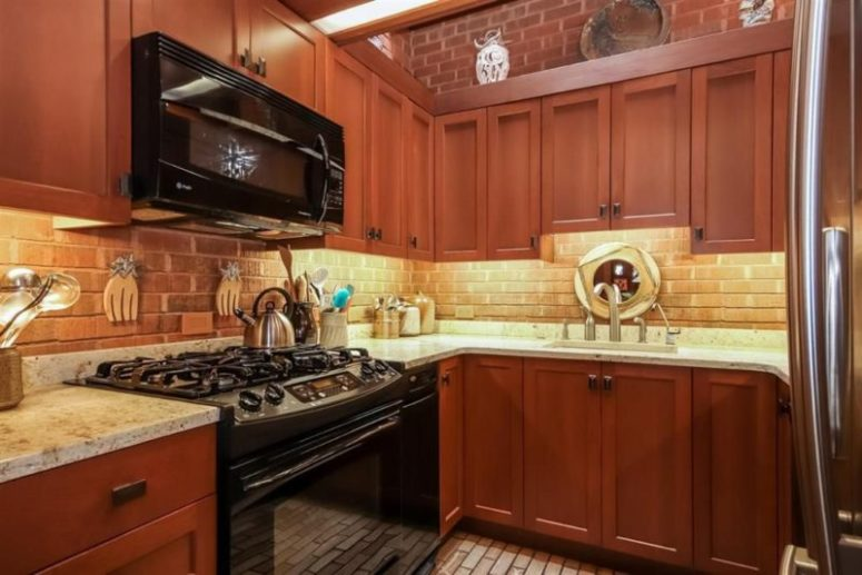 Red wood cabinets with marble countertops create a contrasting look and a brick backsplash adds to the space