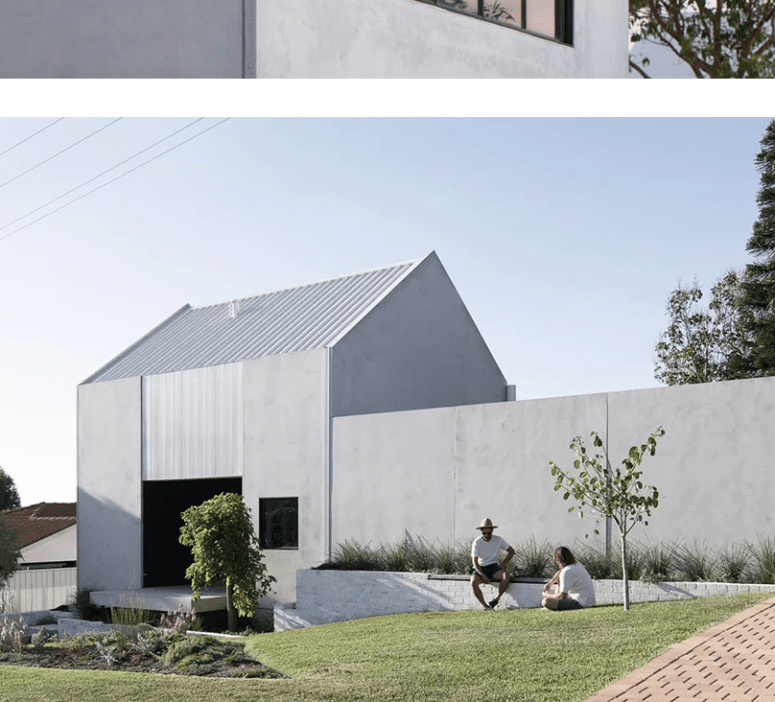 There's an open outdoor space with a lawn and a large brick clad planter with a bench built-in