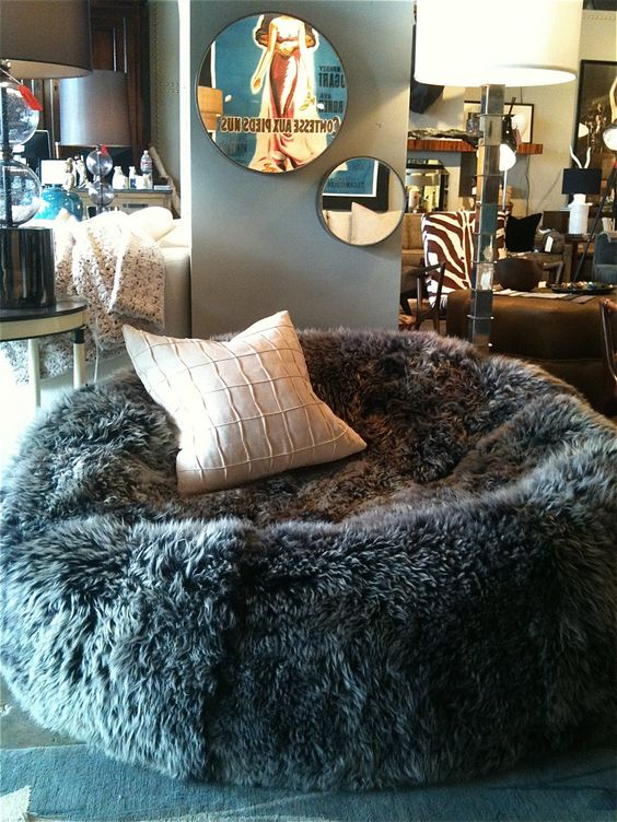 a faux sheep skin bean bag chair with a pillow cna be used both as a chair or as a lounger