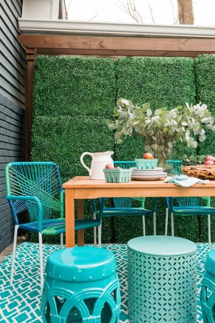 a neutral wooden table and bright turquoise string covered chairs for a modern space