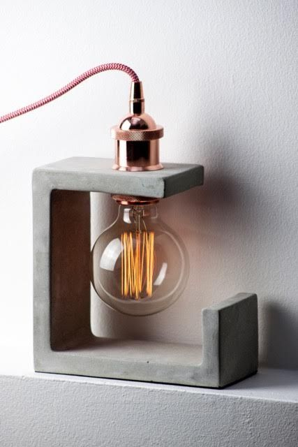 a sculptural concrete table lamps with a copper bulb for a unique look