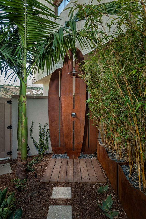 an outdoor shower space with a small wooden deck and metal surfboards plus palms around it