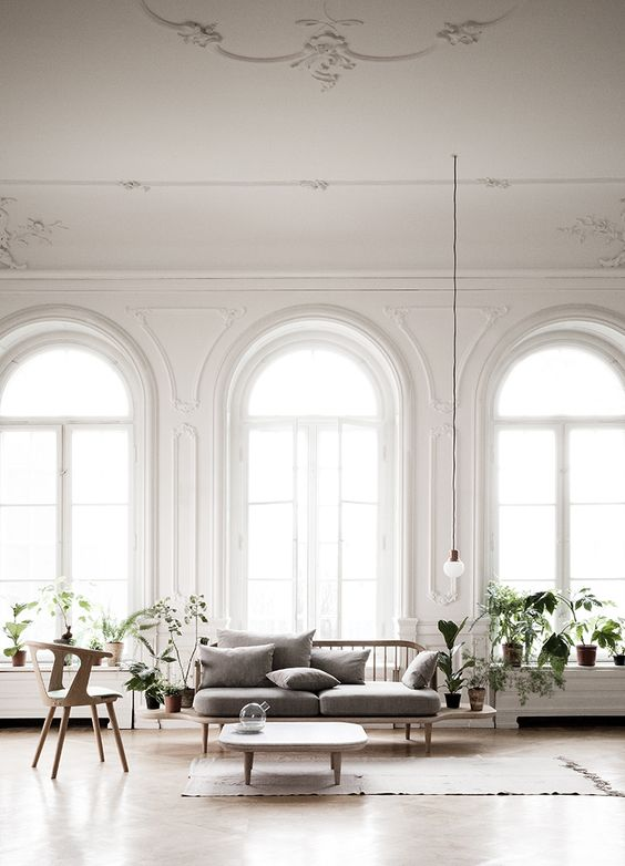 arched floor to ceiling windows create a refined and chic feeling in the space