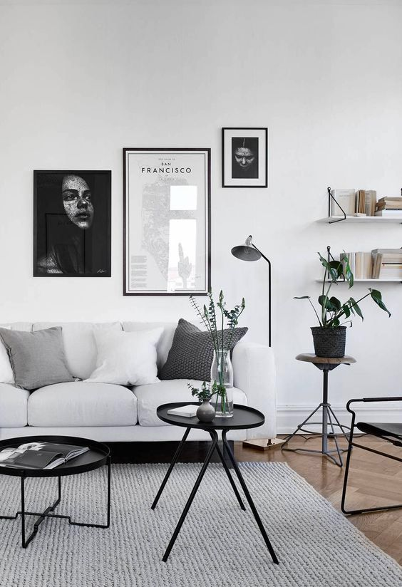 black framed asymmetrical gallery wall is highlighted with black legged furniture and surfaces