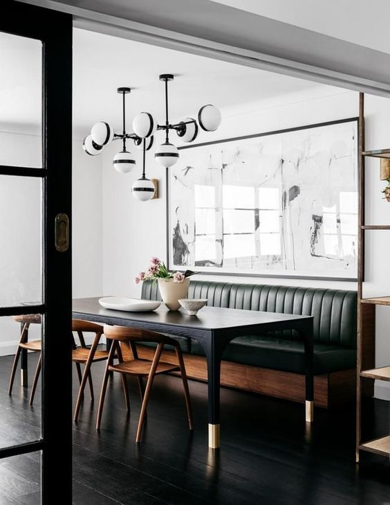 a mid century modern space with a green leather banquette seating and a black table