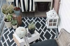 11 a monochromatic balcony with wicker and wooden furniture, black and white textiles, potted plants and candle lanterns