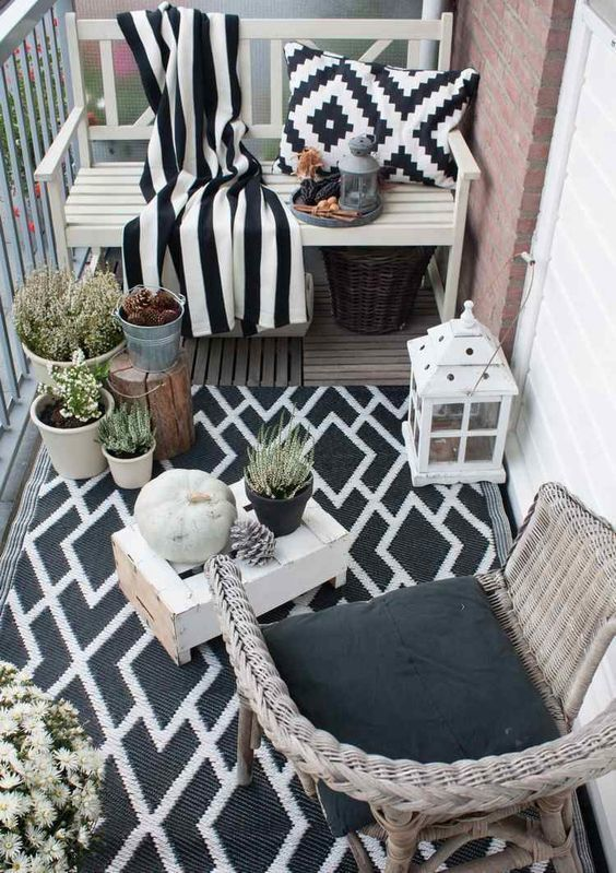 a monochromatic balcony with wicker and wooden furniture, black and white textiles, potted plants and candle lanterns