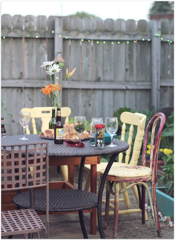a rounf wicker table and all mismatching chairs, shabby and rustic ones in different colors