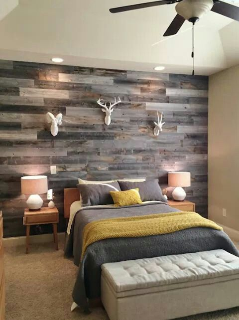 a rustic woodland guest bedroom with a weathered wood plank wall and faux taxidermy for creating an ambience