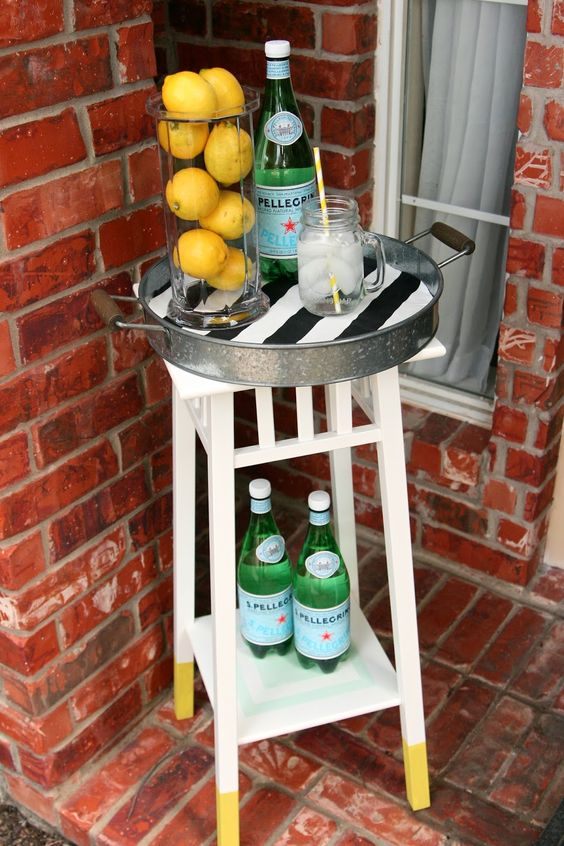 a small bar cart made of an IKEa plant stand and a metal tray is ideal for a tiny outdoor space