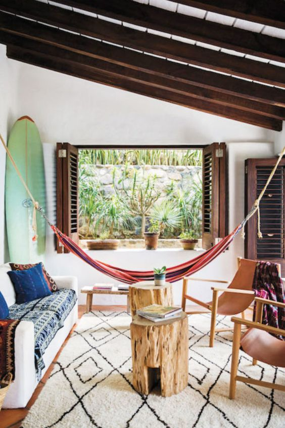 a tropical living room with a colorful striped hammock, a surf and dark stained shutters