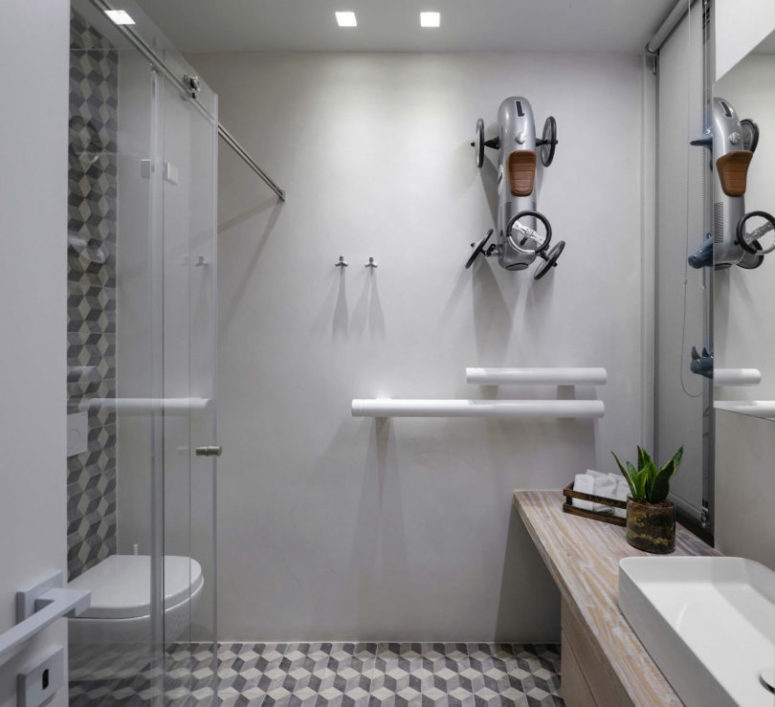 The second bathroom is done with geometric tiles and a large car toy on the wall