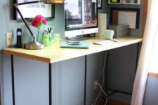 12 a large yet simple standing desk of blakc piping and a wooden countertop