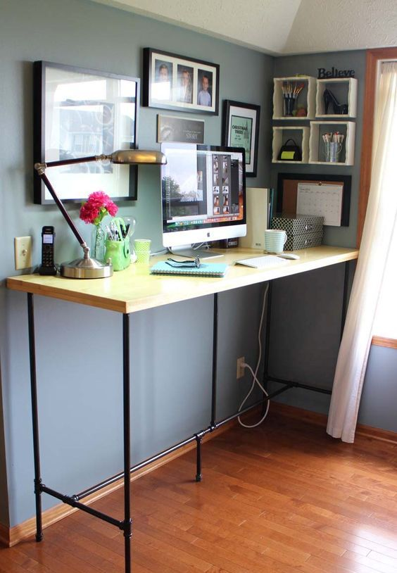 a large yet simple standing desk of blakc piping and a wooden countertop