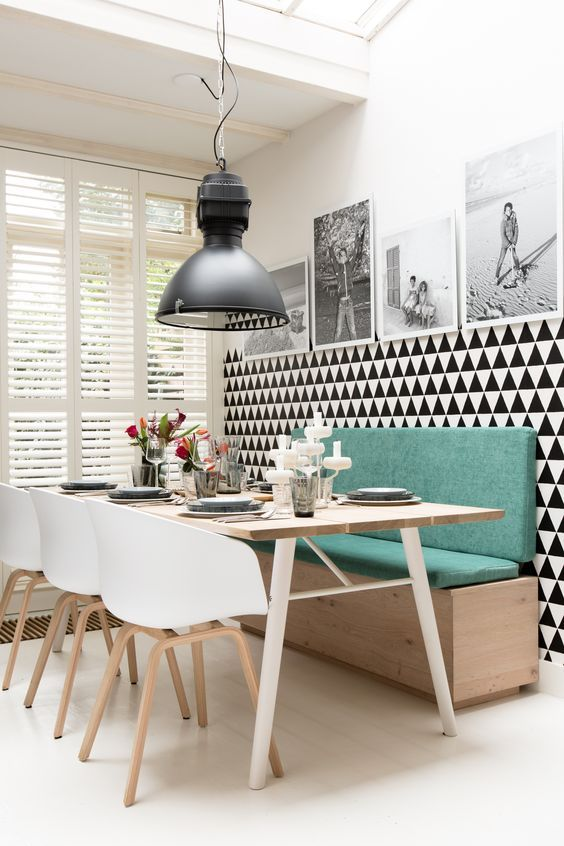 a modern dining space with a green banquette seating and a chevron statement wall