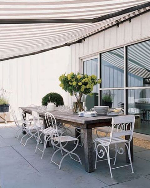 a rough wooden table and white refined and elegant forged chairs for a stylish statement