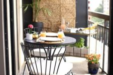 12 a round table, comfy forged chairs, a stand with plants and dishes on top, a jute hanging on the wall