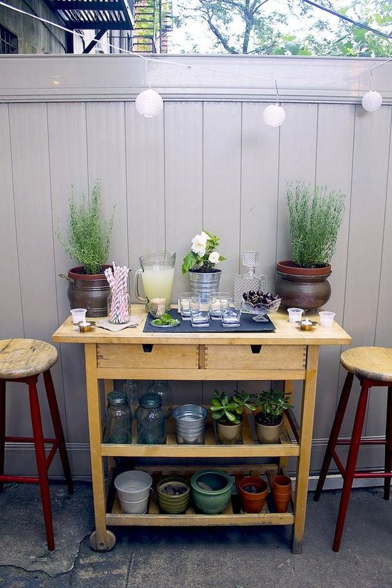 a simple outdoor bar made of an IKEA Forhoja cart painted in a neutral color - such an easy hack doesn't require much skill
